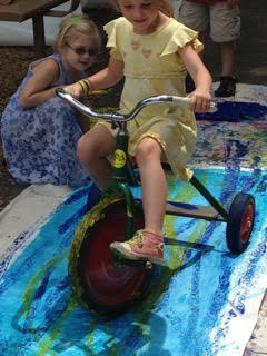 Two Sunshine Nursery School summer camp participants collaborating on an art work with a bike.