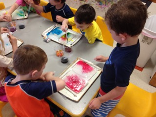 Sunshine Nursery School summer camp participants making beautiful art with water color.