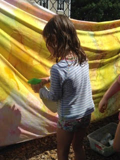 A kid from Sunshine Nursery School's summer camp coloring a cloth.